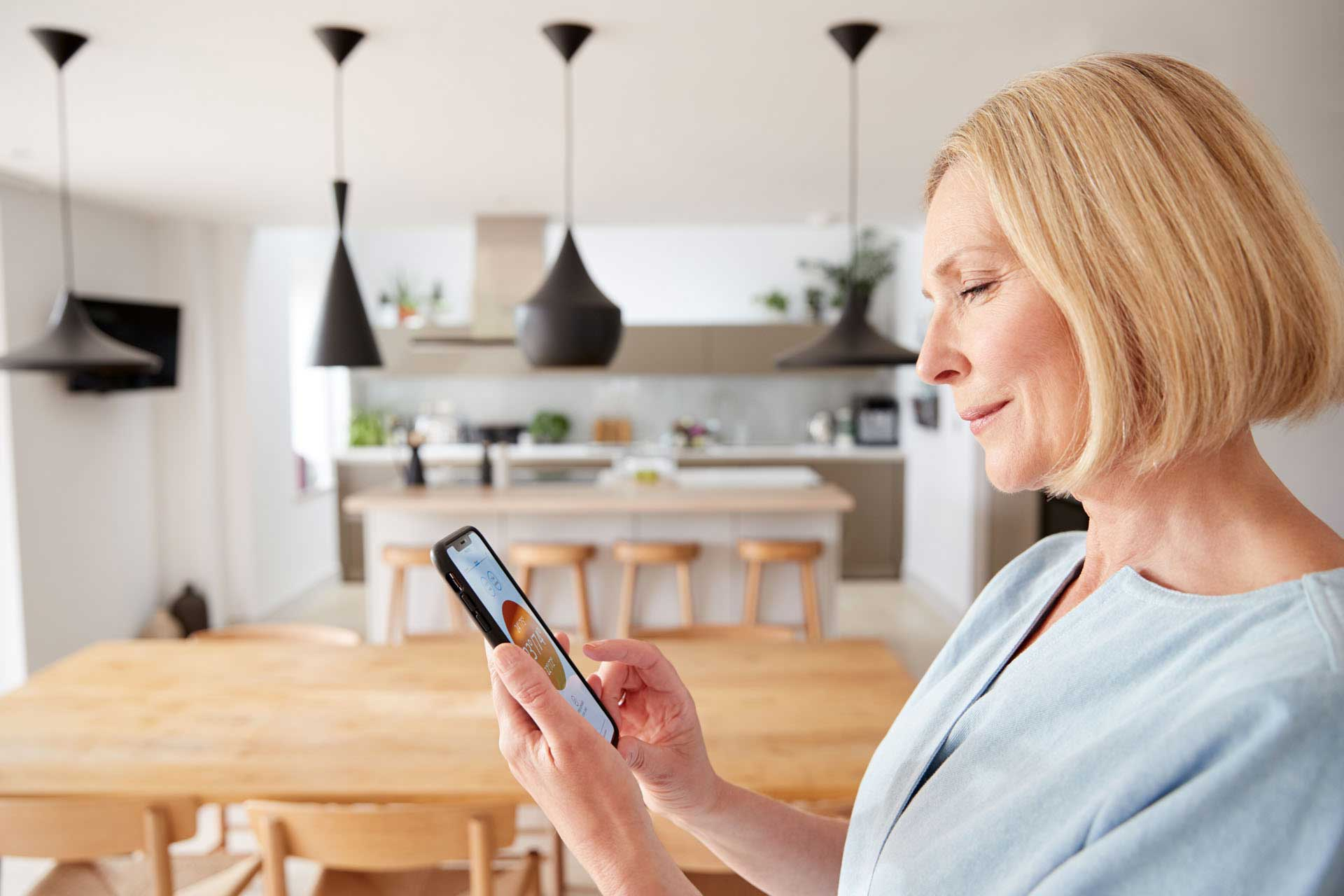 mature woman using app on digital tablet to contro
